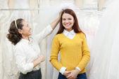Mujer ayuda a la novia en la elección de velo de novia — Foto de Stock