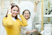 Woman helps the bride in choosing bridal diadem — Stock Photo