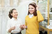 Ekspedientka pomaga panna młoda wybiera suknie ślubne akcesoria — Zdjęcie stockowe