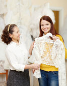 Assistant  helps girl chooses  bridal clothes — Stock Photo