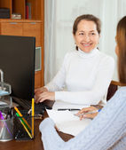 Mature woman talking with employee — Stock Photo