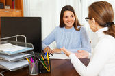 Woman talking to employee with notebook — Stock Photo