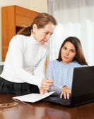 Mature woman and yong daughter with notebook — Stock Photo