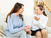 Mother and daughter talking on couch — Stock Photo