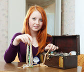 Teen girl chooses jewelry in treasure chest — Stock Photo