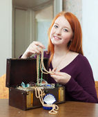 Girl looks jewelry in treasure chest — Stock Photo