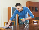Guy dusting wooden table — Stock Photo
