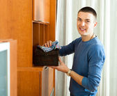Man wiping dust from wooden chest — Stock Photo