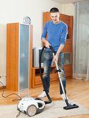 Man with vacuum cleaner  in living room — Photo