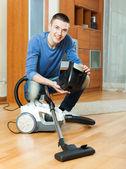 Guy vacuuming  parquet floor — Stock Photo
