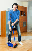 Man sweeping floors in living room — Stock Photo