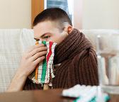 Illness man in scarf using handkerchief — Stock Photo