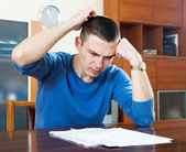 Frustrated man looking at financial document — Stock Photo