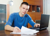 Serious guy staring financial documents — Stock Photo
