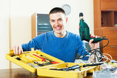 Handsome smiling man with toolbox holding drill — Stock Photo