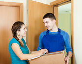 Postman in uniform delivered parcel to woman — Stock Photo
