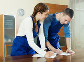 Workers in uniform filling in questionnaire — Stock Photo