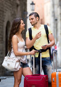 Smiling  young travellers finding path with phone — Stock Photo