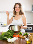 Ordinary long-haired  woman cooking  soup — Stock Photo