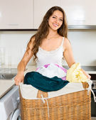 Smiling young woman washing clothes in washer — Stock Photo