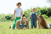 Parents with children laying in the grass — Stock Photo