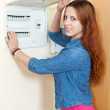 Smiling woman turning off the light-switch — Stock Photo