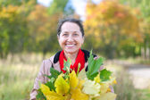 Mature woman  with maple posy — Stock Photo