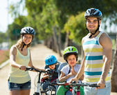 Family of four cycling on street — Stock Photo
