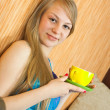 Girl sitting drinking coffee on sofa — Stock Photo #9004224
