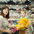 Woman with child chooses baby shoes — Stock Photo #9891408