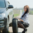 Woman during wheel changing — Stock Photo #9911360