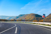 Mountain road bright autumn day with blue sky — 图库照片