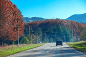 Car moving on the mountain road in autumn sunday — Foto Stock