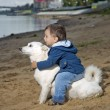 图库照片: Kid sits on dog