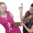 Two young girls having fun putting make up — Stock Photo