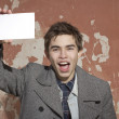 The young man holds a pure sheet of paper — Stock Photo #13496306
