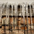 Ice icicles against a brick wall — Stock Photo