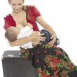 Mother breast feeding her infant sitting on a suitcase — Stok fotoğraf