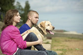 The guy, the girl and dog sit on a beach — Stock Photo