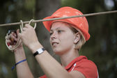 The girl in a helmet hangs on the tense rope — Stock Photo