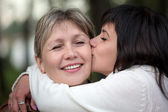 The girl embraces and kisses the woman — Stock Photo