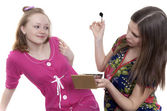 Two young girls having fun putting make up — Stockfoto