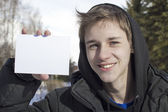 The young man holds a pure sheet of paper — Stock Photo
