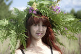 Close-up portrait of beautiful girl with floral wreath on a head — Stock Photo