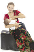 Mother breast feeding her infant sitting on a suitcase — Stock Photo