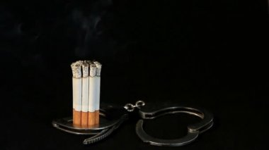 Smoldering cigarette in handcuffs on black background, Timelapse — Stock Video