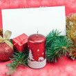 Christmas decorations with card on red — Stock Photo