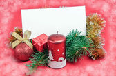Christmas decorations with card on red — Stok fotoğraf