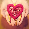 Red heart of colored beads in hands — Stock Photo