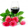 Red wine in glass and pink roses - Stock Photo